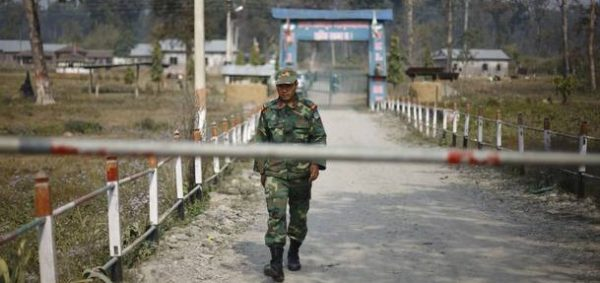 A soldier of Nepal's People's Liberation Army (PLA) walks in front of a Maoist camp at Shaktikhor cantonment in Chitwan, about 160 km (99 miles) south of Kathmandu, February 3, 2012. The first group of the 7,365 former Maoist rebels who opted for voluntary retirement instead of being integrated into the Nepali security forces were discharged on Friday. REUTERS/Navesh Chitrakar