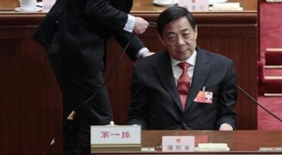China's Chongqing Municipality Communist Party Secretary Bo Xilai pauses, as a man adjusts a cable behind him, during the closing ceremony of the National People's Congress (NPC) at the Great Hall of the People in Beijing March 14, 2012. REUTERS/Jason Lee